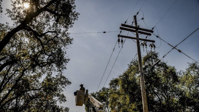 PG&E的工人10日在北灣納巴縣,清理倒在電線上的樹枝。(電視新聞截圖)