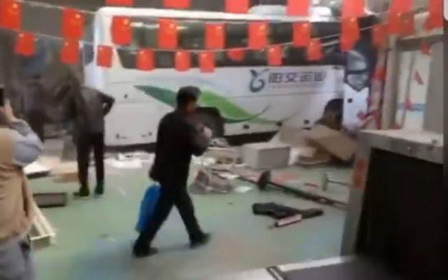 白色大客車部分車頭嵌入牆體,周圍散落許多雜物。(視頻截圖)