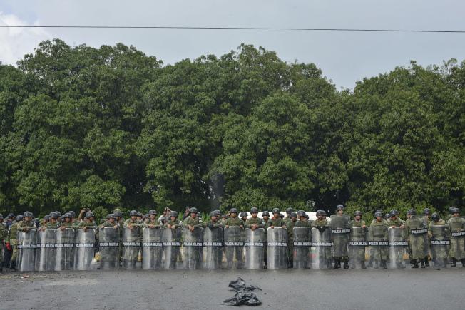 圖為大約500名戴著鋼盔、穿著戰術背心的墨西哥國家衛隊憲兵,封鎖了公路兩端。美聯社