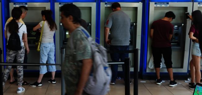 銀行大廳使用自動櫃員機的人潮。(許振輝/攝影)