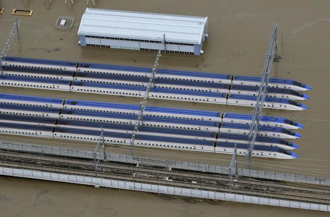 颱風哈吉貝為日本關東、東北地區帶來驚人雨量,數列停放在長野市新幹線車輛中心的子彈列車13日泡在水裡。(美聯社)