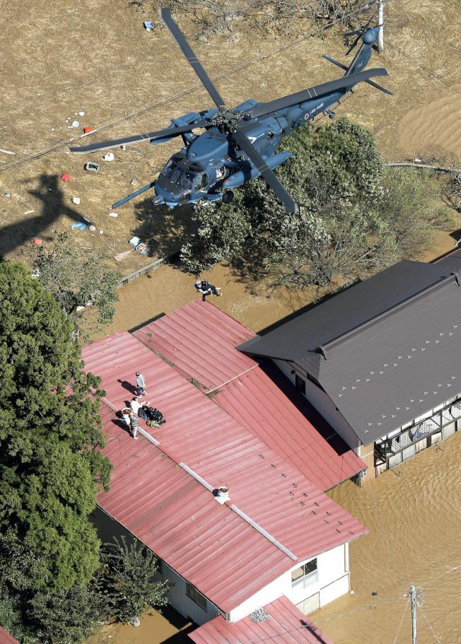 哈吉貝颱風帶來大雨,讓日本東北部宮城縣丸森町淹水,居民13日在屋頂上等待直升機救援。(美聯社)