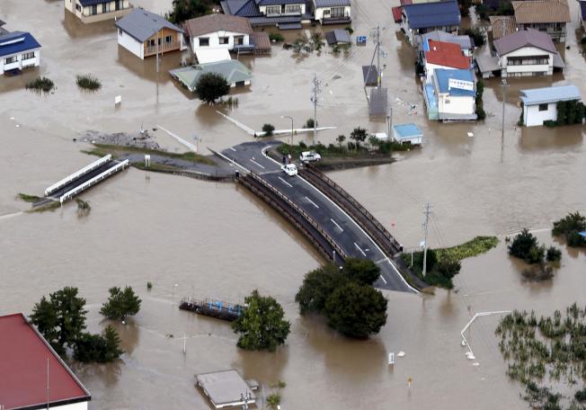 哈吉貝颱風帶來大雨,造成日本中部長野市信濃川堤防潰決,長野市13日泡在泥水中。(美聯社)