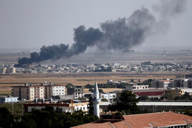 從土耳其城市撤冷彼諾,13日隔著土敘邊界可看見敘利亞北部城市拉斯艾爾安鎮遭到土耳其陸空部隊剿滅攻擊庫德族戰事,空中煙霧瀰漫。(路透)