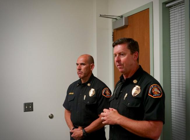 洛杉磯縣消防局調度中心主任Michael Fuentes(左)、洛杉磯縣消防局副局長奧布萊恩(Jon O'Brien)講解調度中心接線員工作流程。(記者陳開/攝影)