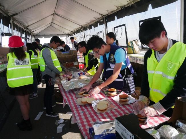 黃博騰(右一)和其他志願者負責做漢堡。(記者梁雨辰/攝影)