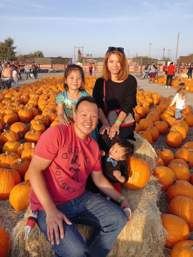 吳育芬(後排右)一家趁著周末,帶小孩到南瓜園遊玩。(記者李榮/攝影)