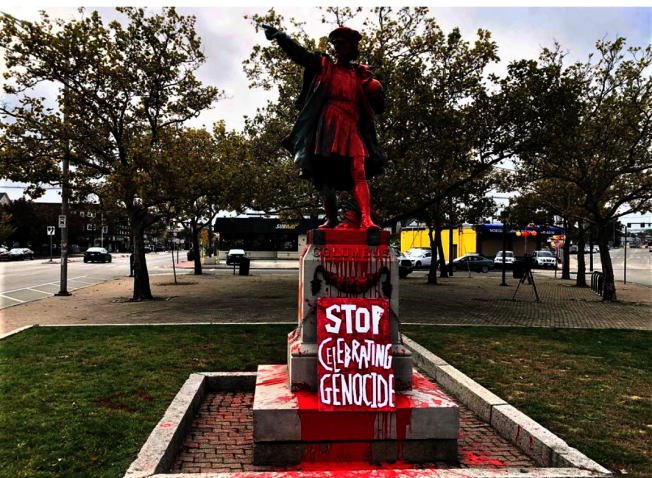 羅島州普維頓斯市的哥倫布雕像14日遭人潑漆。(美聯社)