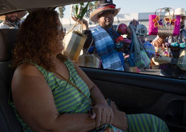墨西哥邊界城市提璜納的醫療觀光已打出名氣,到這裡尋求醫療的人絡繹不絕。圖為美國人梅瑞兒在提璜納做完縮胃手術後,搭車前往美墨邊界關口。(Getty Images)