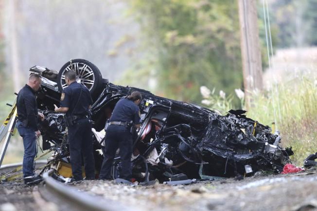 一輛保時捷休旅車在紐約304號公路發生車禍,從高架橋墜落到下面的火車軌道,並當場爆炸,釀成兩名少年死亡、一名少女燒成重傷的悲劇。圖為警方查看燒毀的休旅車。(美聯社)