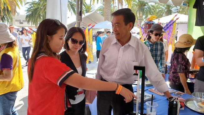 橙縣華僑文教中心主任蔣翼鵬夫婦(左1、2)參加爾灣地球村美食藝術節。(橙僑提供)