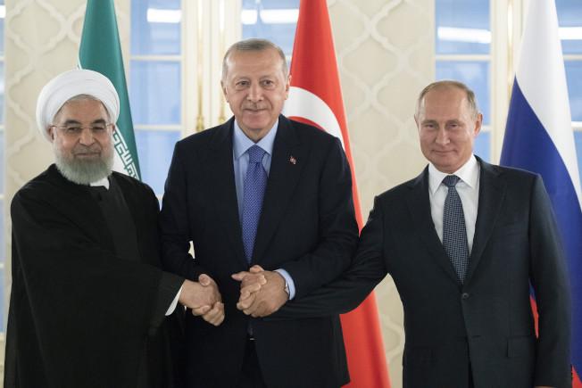川普總統任意而為的撤軍政策,造成敘利亞地區局勢混亂。反而讓伊朗、土耳其、敘利亞及俄羅斯,四國得益。圖為今年9月伊朗總統拉哈尼(左起)、土耳其總統厄多安、俄國總統普亭,在安卡拉舉行三邊會議,共商敘利亞局勢。(美聯社)