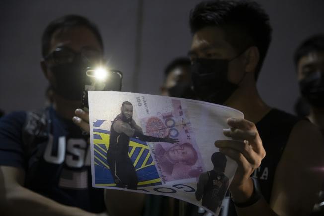 一名香港人15日在示威遊行中手持標語,諷詹姆斯擁抱人民幣。(美聯社)