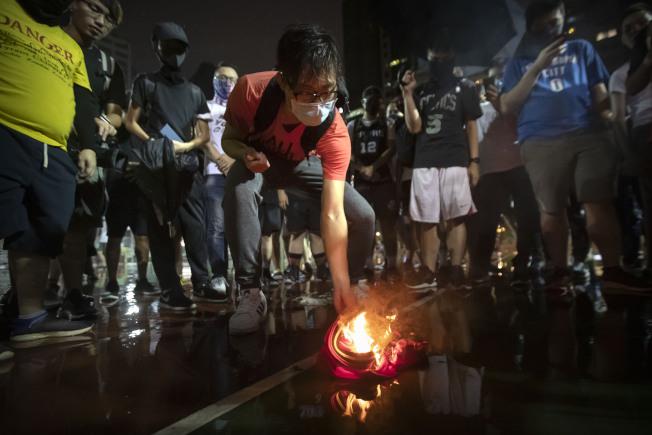 部分香港民眾在得知詹姆斯的發言後,15日燃燒詹姆斯的球衣抗議。(美聯社)