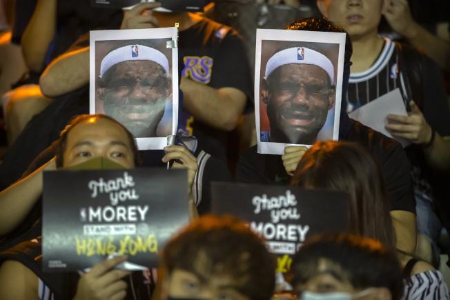 香港街頭15日示威群眾中,有不少人拿著詹姆斯的照片抗議。(美聯社)