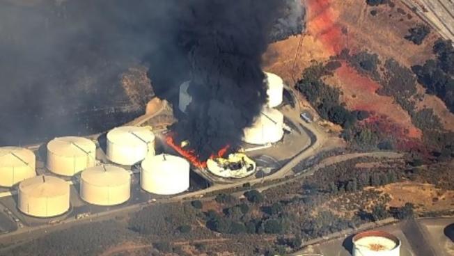 東灣克洛克特市(Crockett)的兩個巨型儲油庫,15日下午發生大火,空前濃密的黑煙天而起。(電視新聞截圖)