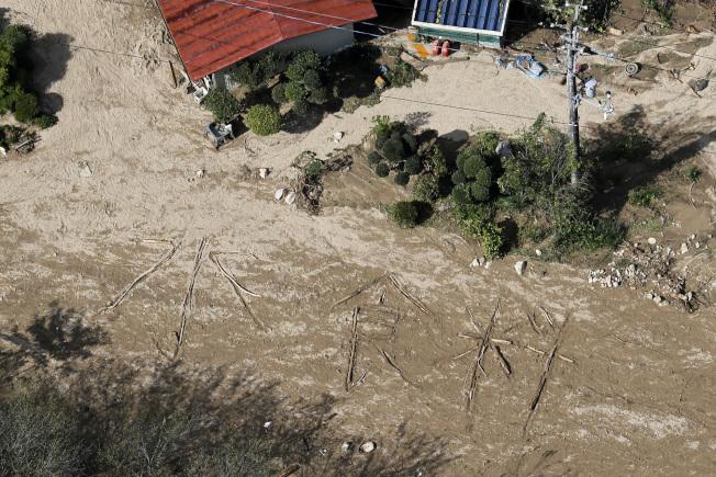 宮城縣丸森町筆甫區一處民居前,有人用倒木或漂流木排成「水、食物」兩組大字,被傳媒採訪直升機發現。(美聯社)