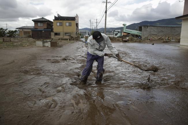 颱風哈吉貝吹襲過後的重災區長野縣15日滿目瘡痍,一名男子清理家園拿鏟子鏟爛泥。 (美聯社)