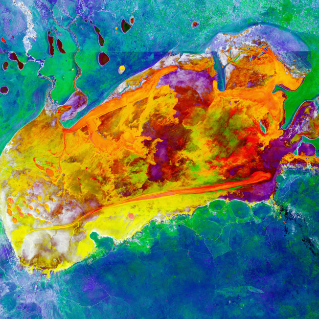 南非國家納米比亞這片廣闊的地區,是世界上最大的鹽田之一,位在埃托沙國家公園內。照片上方一條明顯的水平線條,就是國家公園的圍欄。這張宛如抽象畫的照片,斑斕的色彩代表每次雨季後,水分蒸發,地上鹽分分布的變化。周圍的藍綠色陰影,則是包圍著鹽田的叢林大草原。美國地質調查局