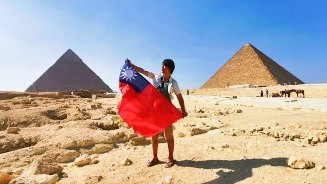 台灣青年楊翰傑拿著國旗環遊世界。圖/楊翰傑提供