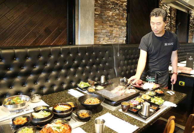 熟達店東一邊烤肉一邊解釋不同部位的肉類配得蘸料,可提升風味。