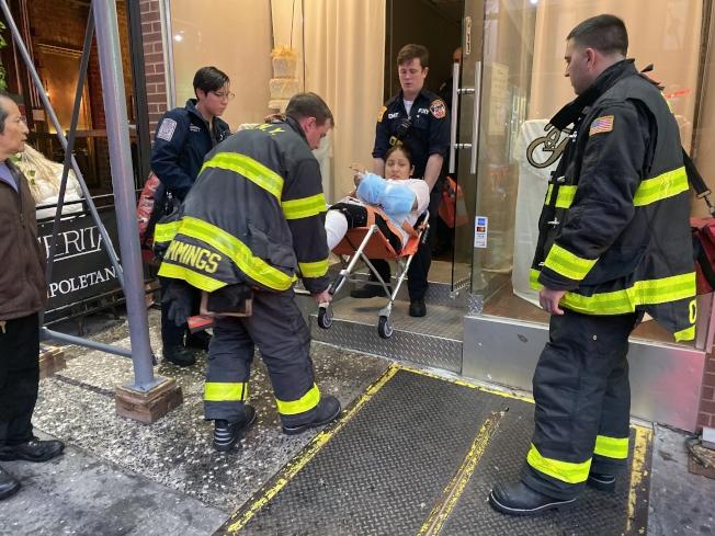 西語裔女員工四肢燒傷被抬出店外。(記者張晨/攝影)