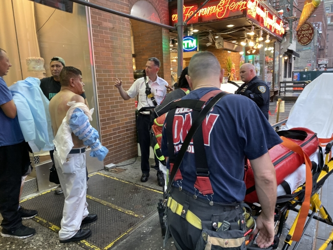 一人名店內員工手臂受傷,等待救援人員安排送醫。(記者張晨/攝影)