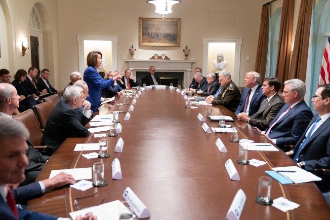 川普總統16日晚推文,貼出白宮攝影師所攝、當天在白宮與國會兩黨領袖開會照片。圖左為民主黨人,右為川普總統及內閣成員。川普在會中說明敘利亞撤軍決策,事後推文稱眾院議長波洛西(立者)演出走樣「完全崩潰」。民主黨則嚴辭批評川普失控。(取自川普推文)