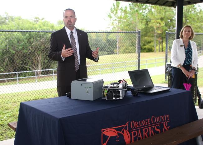 橘郡公園管理處經理Matt Suedmeyer展示新的監控攝像頭。(橘郡提供)