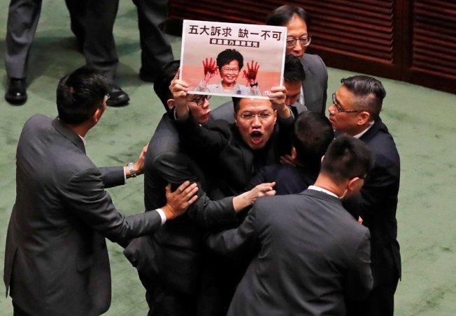 香港泛民主派議員昨天在特首林鄭月娥到立法會出席施政報告答問大會時,不斷高呼口號抗議。 (路透)