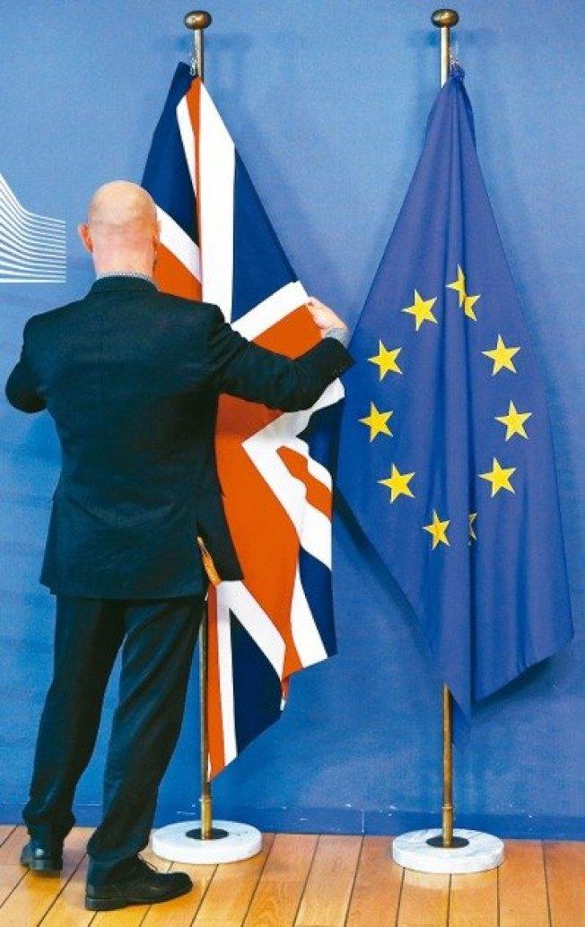 歐盟執委會主席容克與英國首相強生17日舉行聯合記者會前,歐盟工作人員調整英國國旗與歐盟旗幟的位置。 (路透)