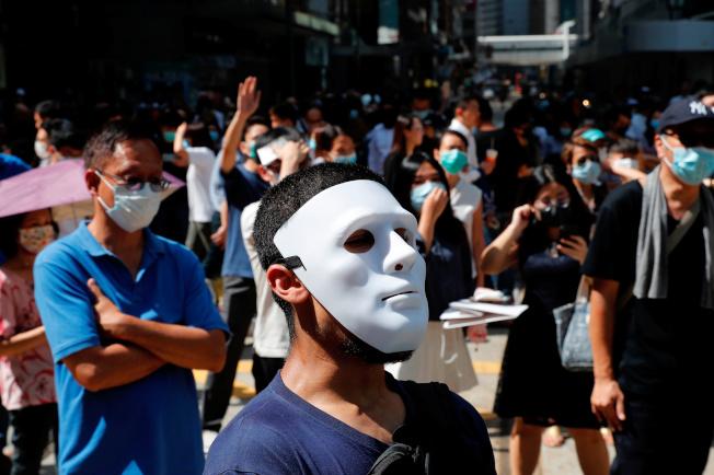 香港人戴上口罩面具上街示威,和電影《小丑》情景不謀而合。(路透)