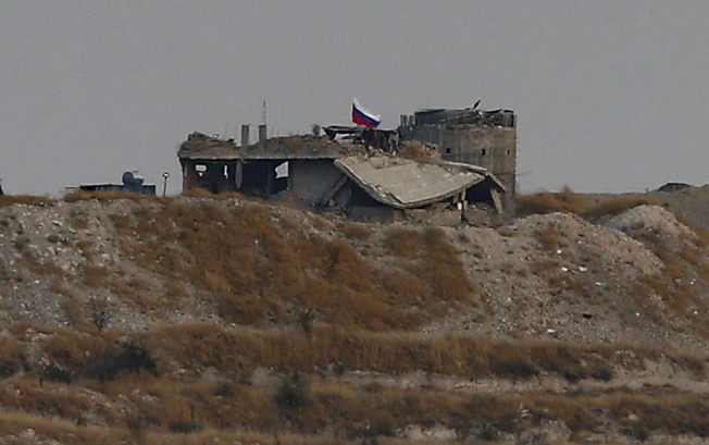 敘利亞北部已可見到俄羅斯部隊進駐升旗,他們應敘利亞政府之請,擔任與土耳其間的協調人。(美聯社)