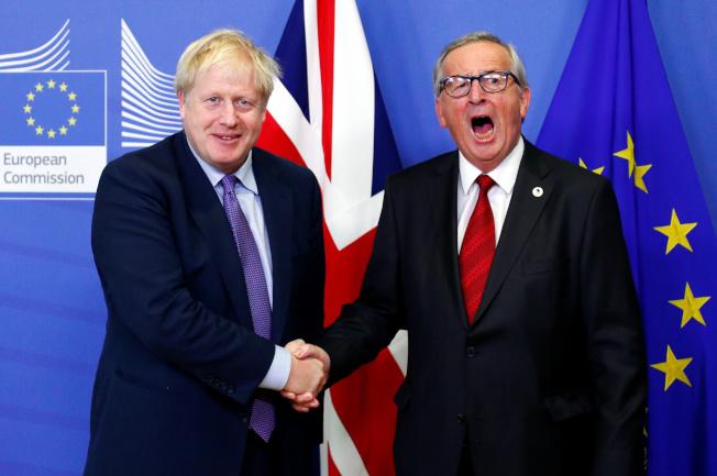 英國首相強生(左)與歐盟執委會主席容克(右)17日在歐盟總部舉行聯合記者會,宣布雙方達成脫歐協議。(路透)