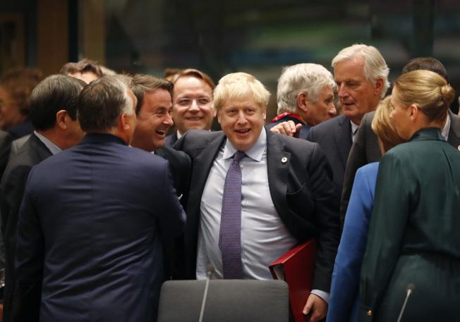 歐盟17日通過英國脫歐條件,各國領袖向英國首相強生(中)道賀,但還須英國議會通過。(美聯社)