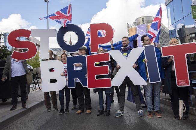 反對脫歐的英國民眾17日在街頭抬著「停止脫歐」標語在布魯塞爾街頭抗議,顯示強生首相在議會通過脫歐的阻力仍不小。(美聯社)