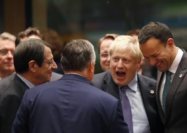 英相強生(前右二)17日在歐盟通過英國脫歐條件時,與愛爾蘭總理瓦拉德卡(右一)、匈牙利總理奧班(中)握手。(美聯社)