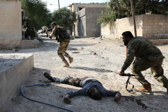 儘管達成停火協議,土耳其仍然砲擊敘利亞境內的庫德族據點。圖為土軍砲火擊斃一名庫德族人,周圍的庫德族戰士連忙尋找掩蔽。(Getty Images)