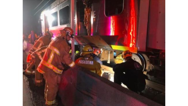 金線(Gold line)巴沙迪那車站18日淩晨發生車禍,一名乘客不慎跌入軌道被捲入輕軌底部,所幸被消防員救出,但傷情嚴重。(洛杉磯縣消防局提供)