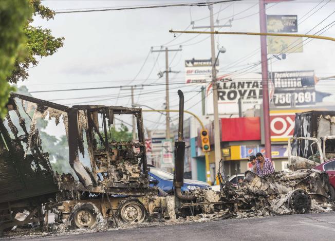 毒梟焚燒車輛作為路障,阻擋政府軍靠近。(美聯社)
