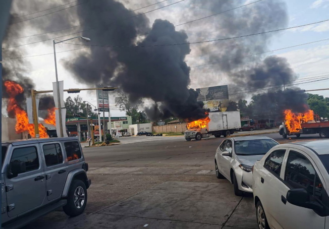 墨西哥安全部隊於17日在古里亞坎市拘捕大毒梟「矮子」古茲曼之子,和販毒集團成員發生槍戰時,街頭車輛起火燃燒。(歐新社)