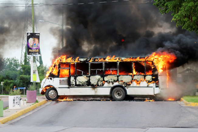 墨西哥安全部隊17日拘捕大毒梟「矮子」古茲曼之子時,和販毒集團成員發生槍戰,毒梟將公車橫擋在路中央,點火阻止政府軍靠近。(路透)