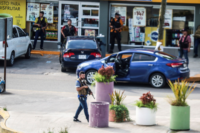 墨西哥安全部隊抓捕大毒梟「矮子」古茲曼之子,和販毒集團槍手發生激烈槍戰,圖為販毒集團的槍手公然在大街上持槍與警方對抗。(路透)