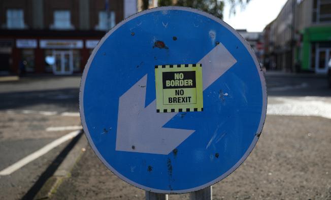 愛爾蘭靠近英國北愛邊界一個交通標誌上,16日貼著貼紙「不要硬邊界,不要英國脫歐」。(路透)
