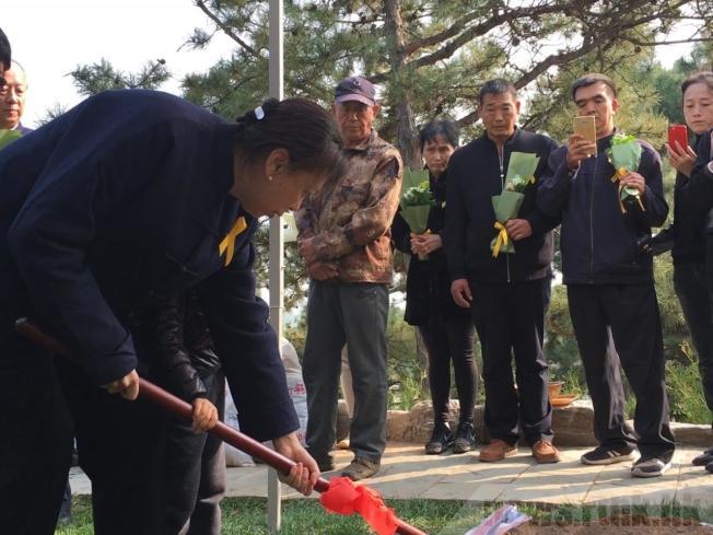 趙紫陽女兒王雁南為墓穴填土。(取材自香港電台)