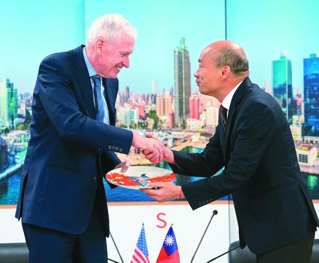 高雄市長韓國瑜(右)18日銷假上班,會見美國在台協會主席莫健(左),兩人閉門會談前公開握手交換禮物,韓國瑜送莫健瓷器盤子。 (記者劉學聖/攝影)