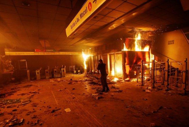 智利首都聖地牙哥民眾近日走上街頭,抗議地鐵票價調漲,但活動18日晚間變調,暴力與破壞四起,一處地鐵售票中心遭到縱火焚燒。路透