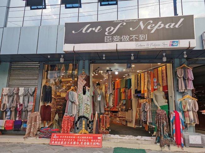 位在尼泊爾第2大城市波卡拉(Pokhara)街上,販售傳統服飾的店家在招牌寫上中文名稱,店門口的牌子也用中文寫上「來到這家店不買圍巾,臣妾做不到啊!」藉此吸引目光。圖/中央社