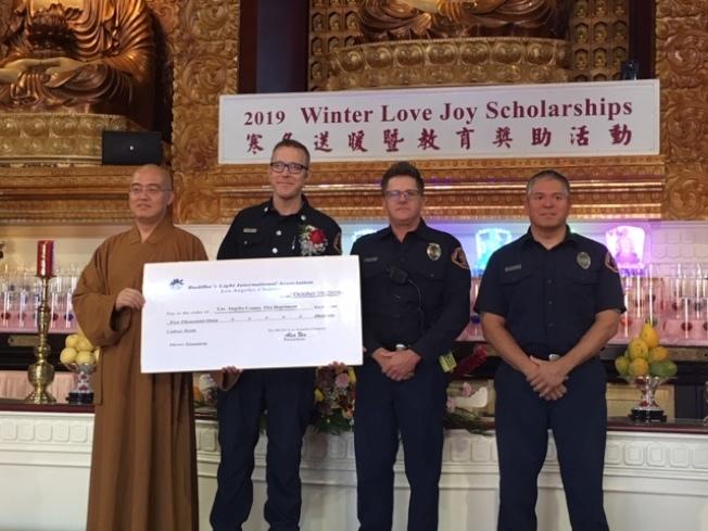西來寺惠東法師(左)在「寒冬送暖暨教育獎助活動」上向洛杉磯縣警察局贈送2000元支票,感謝常年對社區的服務。(記者楊青/攝影)