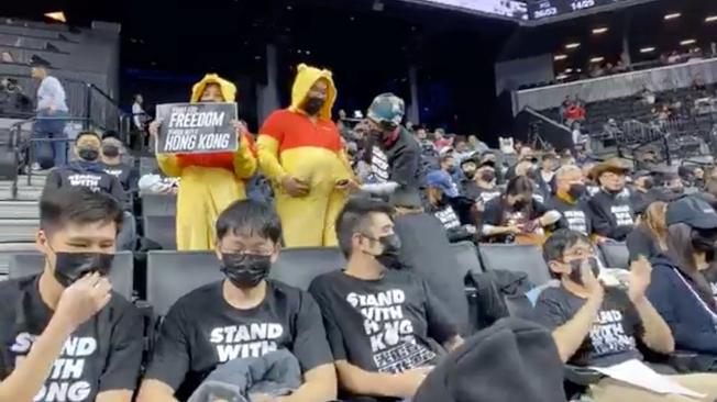 香港反送中抗爭的支持者18日在紐約於NBA職籃布魯克林網隊出賽多倫多暴龍隊時舉牌抗議。路透